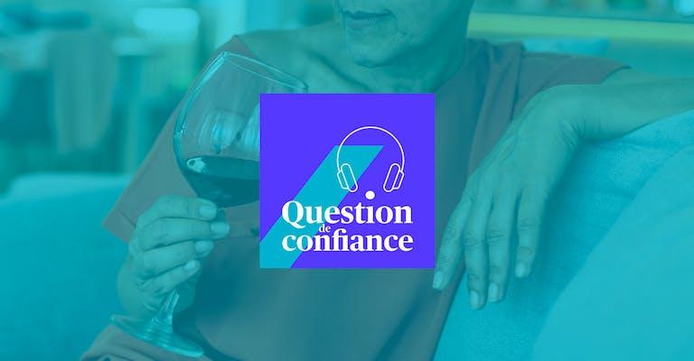 Gros plan sur les mains d'une femme assise dans un canapé tenant un verre à vin. Logo Question de confiance en surimpression.