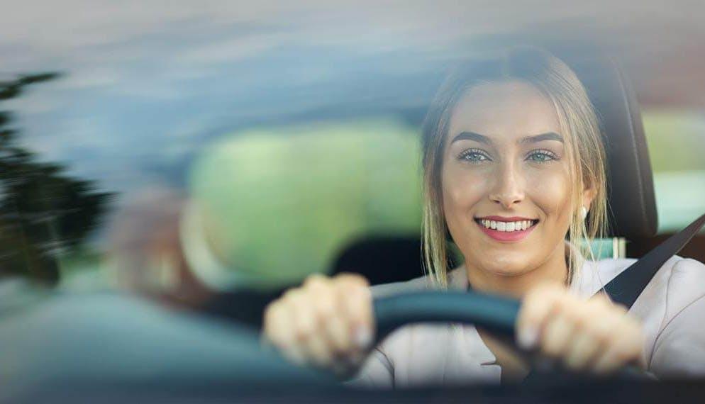 femme avec le sourire au volant d'une voiture
