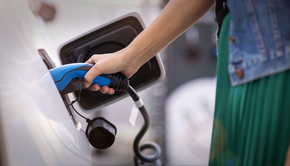 femme en train de charger voiture électrique