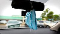 Conduite avec un masque accroché au rétroviseur de sa voiture