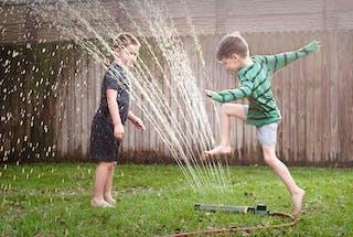 3 enfants jouent avec jet d'eau jardin
