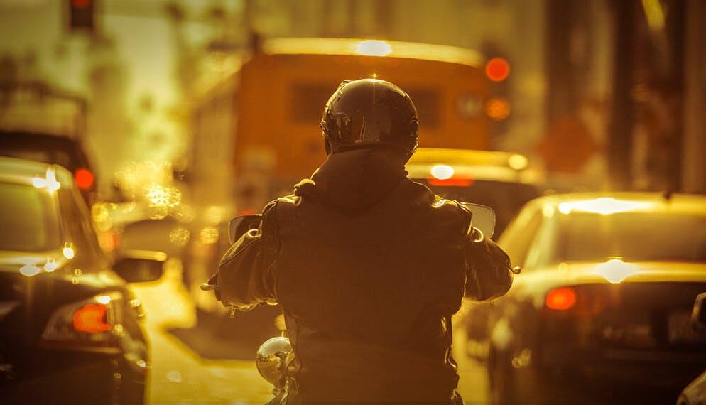 conducteur moto ville entre les voitures