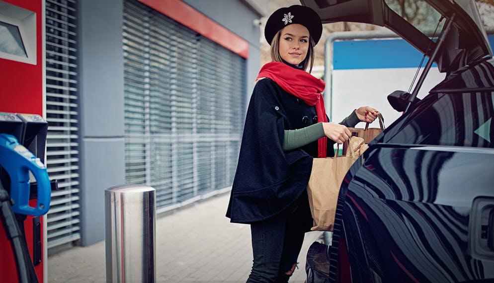jeune femme chargeant ses courses dans sa voiture électrique en charge