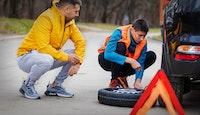 deux hommes en train de changer pneu crevé
