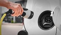 Femme débranchant un chargeur d'une prise de voiture électrique