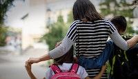 maman entourant ses enfants sur le chemin de l'école